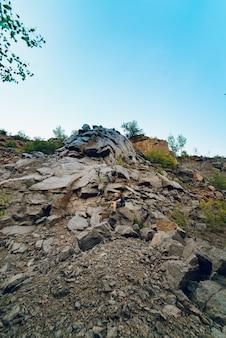 Un turista si trova in alto su una roccia che si trova sulla montagna.