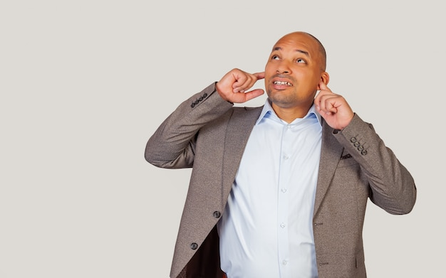 Un uomo afroamericano dalla pelle scura, con irritazione, si tappa le orecchie con le dita, non volendo sentire suoni forti dall'alto