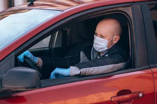 Un uomo alla guida di un'auto in una maschera protettiva medica e guanti. guida sicura in taxi durante un coronavirus pandemico.