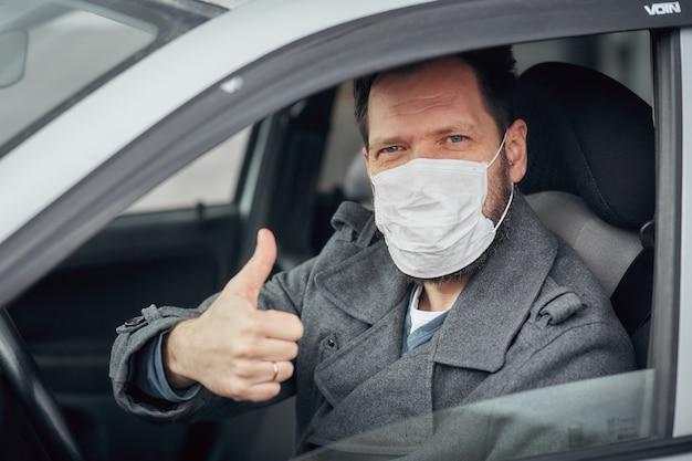 Un uomo alla guida di un'auto indossa una mascherina medica durante un'epidemia, un tassista in maschera, protezione dal virus