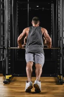 Un uomo allena le braccia e il petto in palestra sul simulatore, fa esercizi
