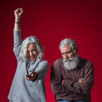 Un uomo anziano arrabbiato con le braccia incrociate tenendo in mano il telecomando tifo su sfondo rosso