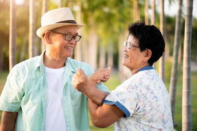 Un uomo anziano asiatico e una donna delle coppie senior felici che sorridono e che ridono nel giardino