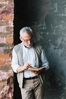 Un uomo anziano che sta davanti al libro di lettura del muro di cemento