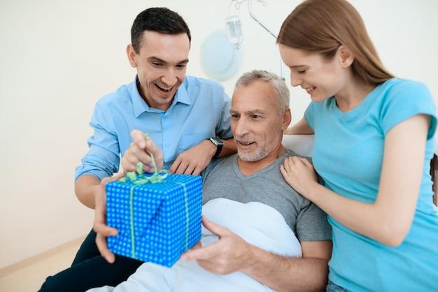 Un uomo anziano giace in una stanza d'ospedale su un letto