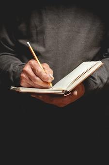 Un uomo anziano ha scritto a matita su un taccuino
