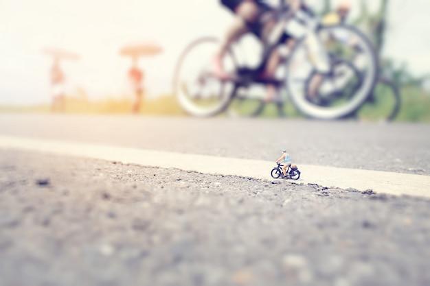 Un uomo anziano (in miniatura) su un giro in bicicletta in una strada di campagna con un gruppo di sfondo di gara ciclistica. fuoco molle e composizione bassa in profondità di campo con colore pastello molle