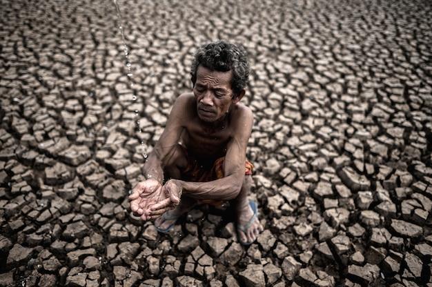 Un uomo anziano seduto in contatto con la pioggia nella stagione secca, riscaldamento globale, messa a fuoco selettiva