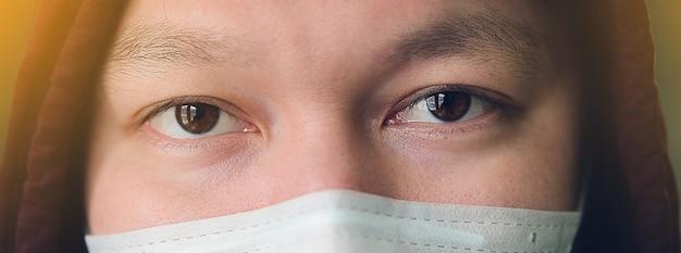 Un uomo asiatico infetto da influenza che indossa una maschera che lo protegge dal coronavirus. il concetto di polmonite, epidemie e pericolo di infezione virale. primo piano del volto dell'uomo.