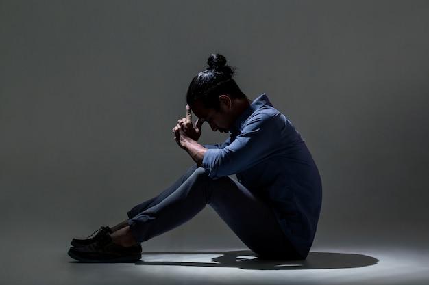 Un uomo asiatico soffre di depressione nell'oscurità.
