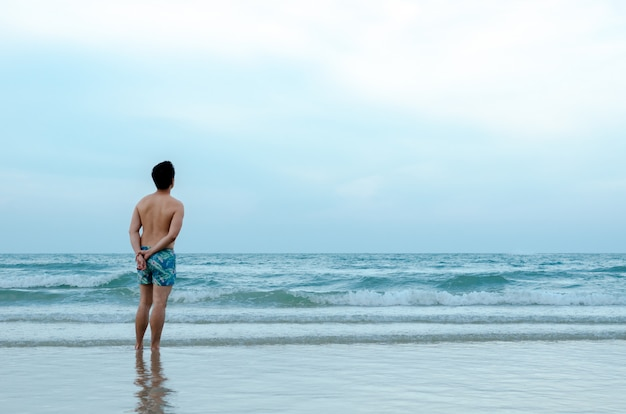 Un uomo asiatico solo stand alone sulla spiaggia