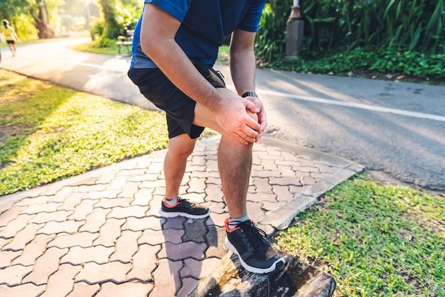 Un uomo attualmente sta avendo un infortunio al ginocchio durante l'esercizio fisico correndo nel parco