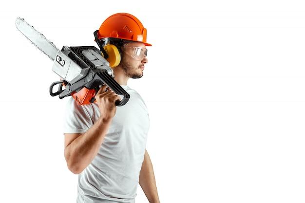 Un uomo barbuto in un casco in possesso di una motosega su uno sfondo bianco.