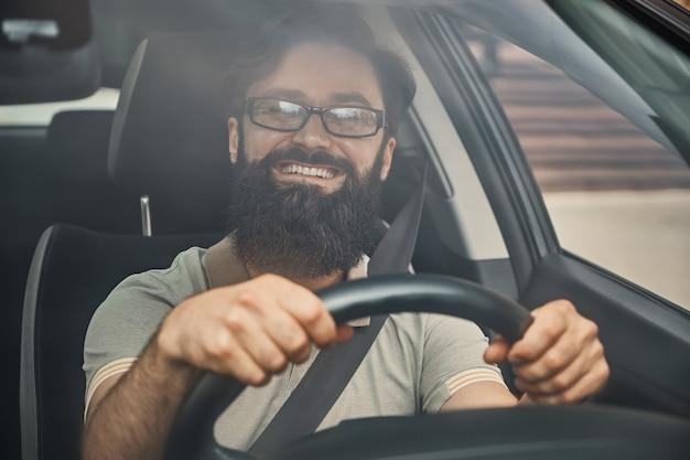 Un uomo barbuto moderno alla guida di un'auto