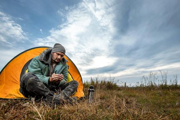 Un uomo barbuto siede in campeggio in una tenda sullo sfondo della natura e del lago. viaggi, turismo, campeggio.