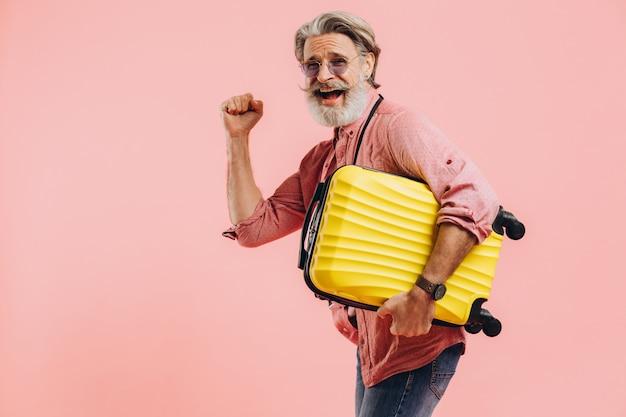 Un uomo barbuto tiene in mano una valigia gialla, sorride e si prepara per il viaggio.