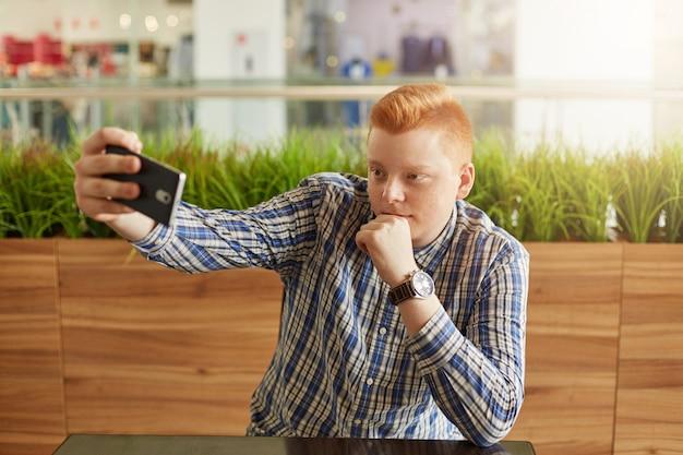 Un uomo bello rossa con taglio di capelli alla moda vestito con camicia elegante a quadri che fa selfie pur avendo un periodo di riposo