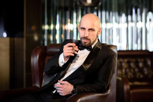 Un uomo brutale in un cappotto di pelliccia fuma un sigaro.