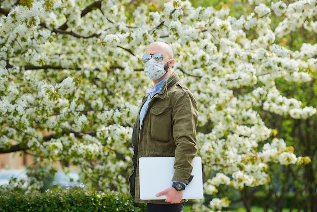 Un uomo calvo con la barba in una maschera medica per evitare la diffusione del coronavirus cammina con un laptop nel parco. un ragazzo indossa una maschera da viso n95 e un occhiale da sole pilota nel giardino tra alberi in fiore.