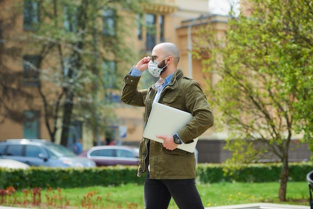 Un uomo calvo con la barba in una maschera medica per evitare la diffusione del coronavirus cammina con un laptop nel parco. un ragazzo indossa una maschera n95 e occhiali da sole da pilota sulla strada della città.