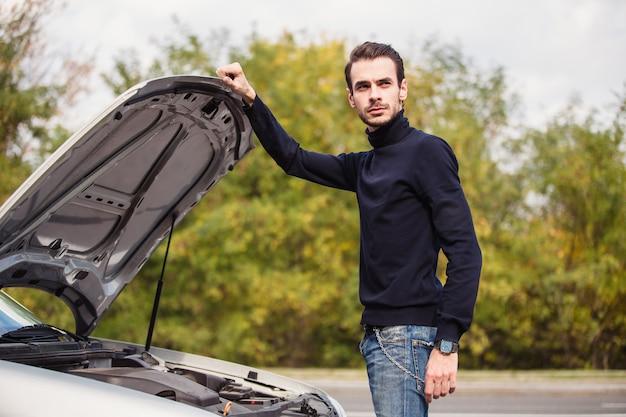 Un uomo cerca di riparare l'auto sulla strada
