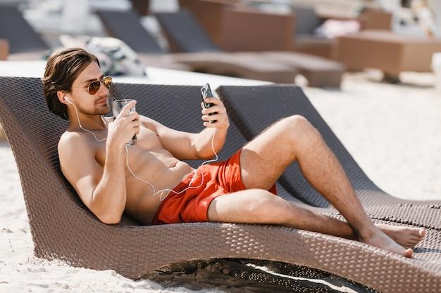 Un uomo che ascolta la musica che prende il sole sulla sedia a sdraio sulla spiaggia