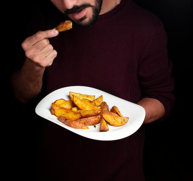 Un uomo che assaggia le patate fritte dal piatto bianco