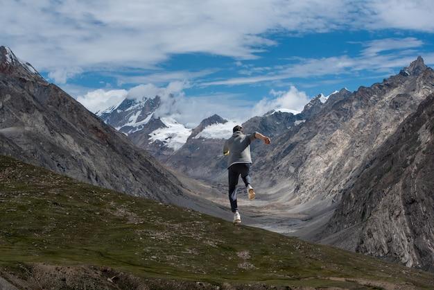 Un uomo che corre in salita fino alla cima della montagna con il cielo blu sullo sfondo