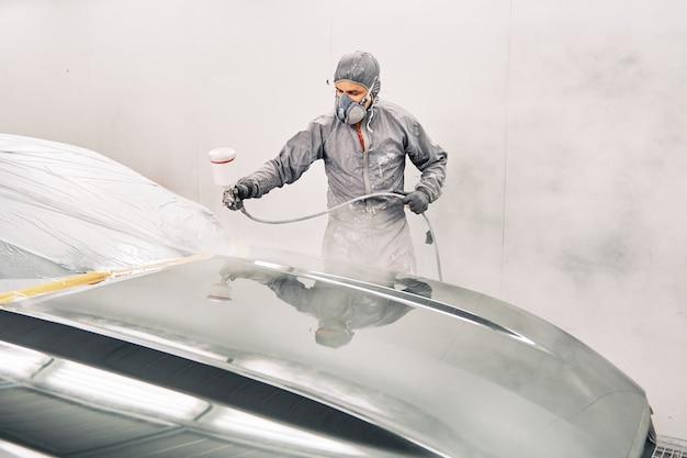 Un uomo che dipinge una macchina