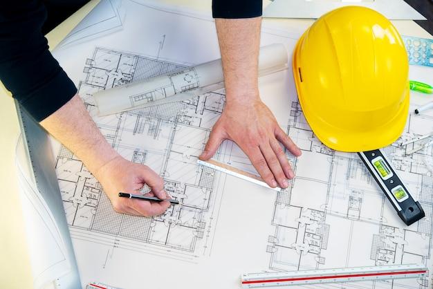 Un uomo che disegna il progetto di una casa
