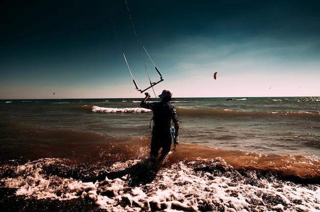 Un uomo che fa volare un aquilone in spiaggia. kite surf