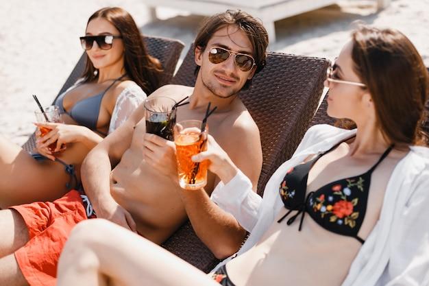 Un uomo che flirta con le ragazze sulla spiaggia