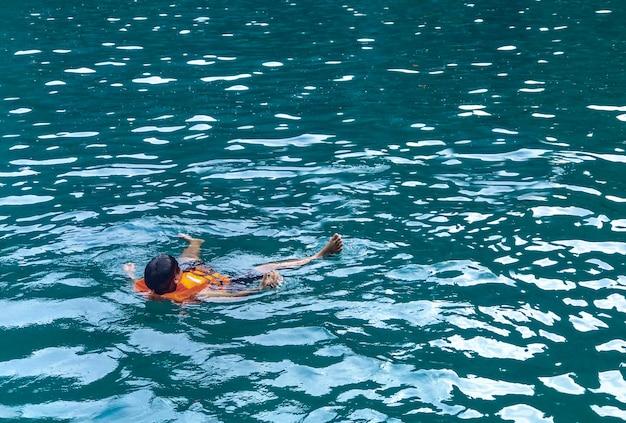 Un uomo che galleggia e si rilassa dall'immersione subacquea del mare all'isola di phi phi.