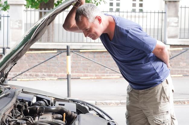 Un uomo che ha un brutto giorno controlla sotto il cofano della sua auto a figu