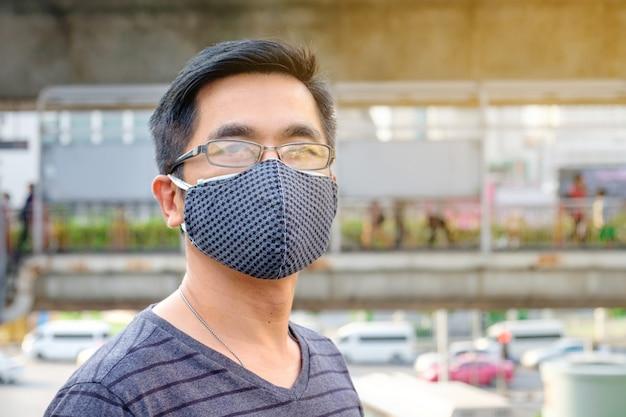 Un uomo che indossa monocolo e maschera nera contro l'inquinamento atmosferico con pm 2,5 a bangkok, thailandia