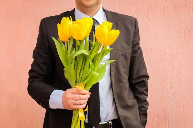 Un uomo che indossa un tailleur, tenendo il mazzo di tulipani gialli.