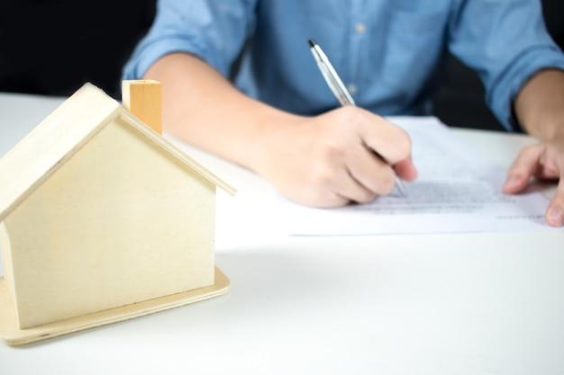 Un uomo che indossa una maglietta in mano una penna e firma un contratto di casa su un tavolo bianco.