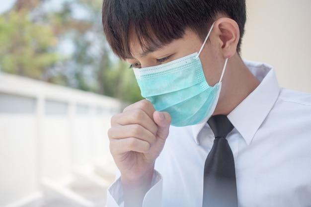 Un uomo che indossa una maschera chirurgica per coprirsi il naso con tosse e starnuti a causa di malattie al fine di prevenire la diffusione di virus e germi ad altri, i thailandesi asiatici usano la maschera facciale in caso di malattia