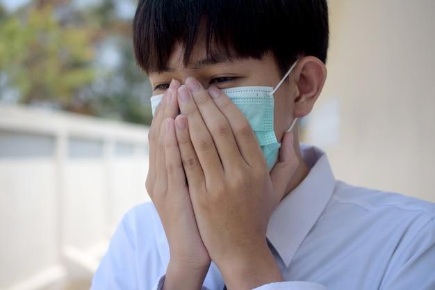 Un uomo che indossa una maschera chirurgica per coprirsi il naso con tosse e starnuti a causa di malattie al fine di prevenire la diffusione di virus e germi ad altri, la maschera per il viso protegge il virus corona 2019