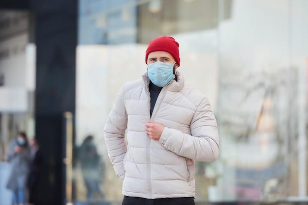 Un uomo che indossa una maschera medica per evitare la diffusione del coronavirus (covid-19).