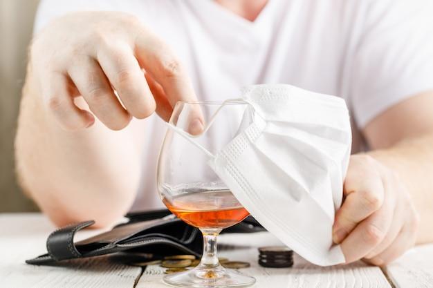 Un uomo che indossa una maschera medicante in posa con un bicchiere di alcol, ritratto al coperto