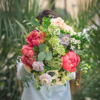 Un uomo che offre un bouquet di fiori estivi colorati.