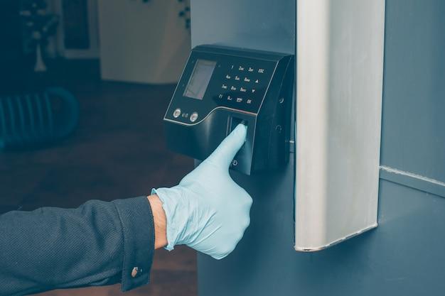 Un uomo che ottiene un citofono per leggere l'impronta digitale per aprire la porta con i guanti.