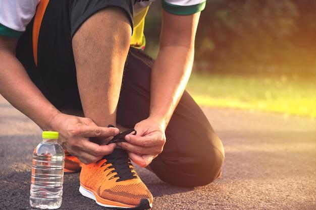 Un uomo che prepara e indossa scarpe sportive per fare jogging e fare esercizio al mattino.