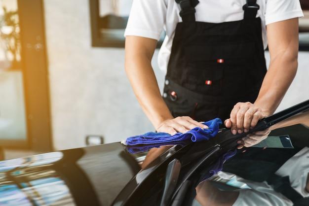 Un uomo che pulisce la macchina e rimuove un graffio con un asciugamano in microfibra blu asciutto