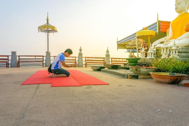 Un uomo che rende omaggio a un grande monaco in uno dei templi