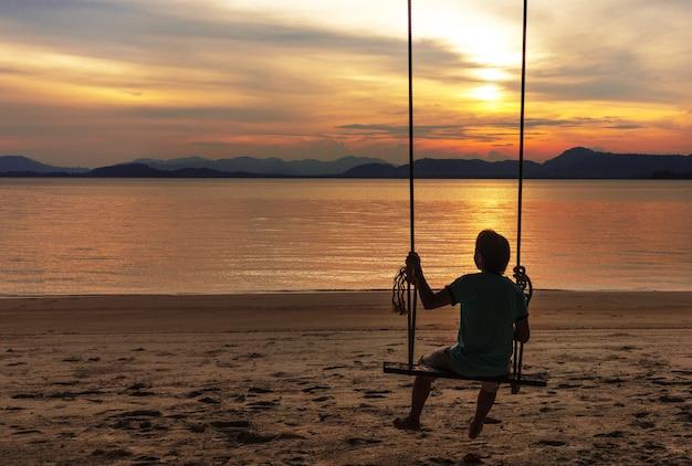 Sezione dame Silverine Un-uomo-che-si-distende-sulla-sedia-a-dondolo-in-legno-guardando-il-tramonto-sulla-spiaggia_25105-3
