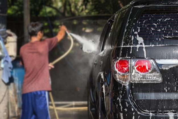 Un uomo che spruzza l'idropulitrice per l'autolavaggio nel negozio di cura dell'auto