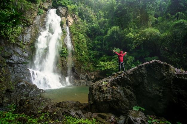Un uomo che sta al concetto di viaggio della cascata