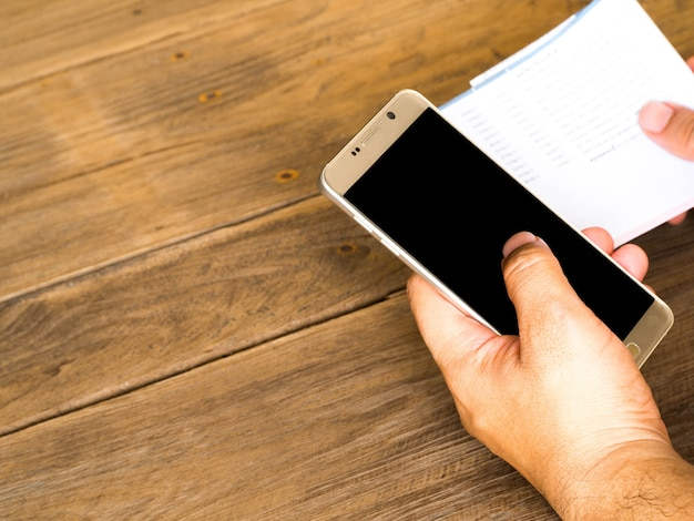 Un uomo che tiene smart phone per l'utilizzo di app banking online per il pagamento del conto della carta di cradit.